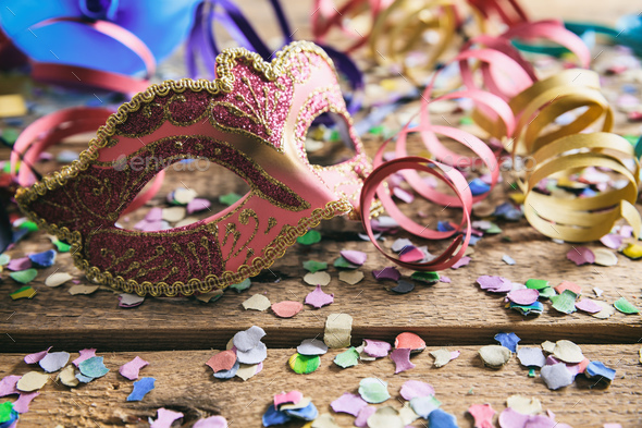 Carnival party. Mask, confetti and serpentines on wooden background, front view